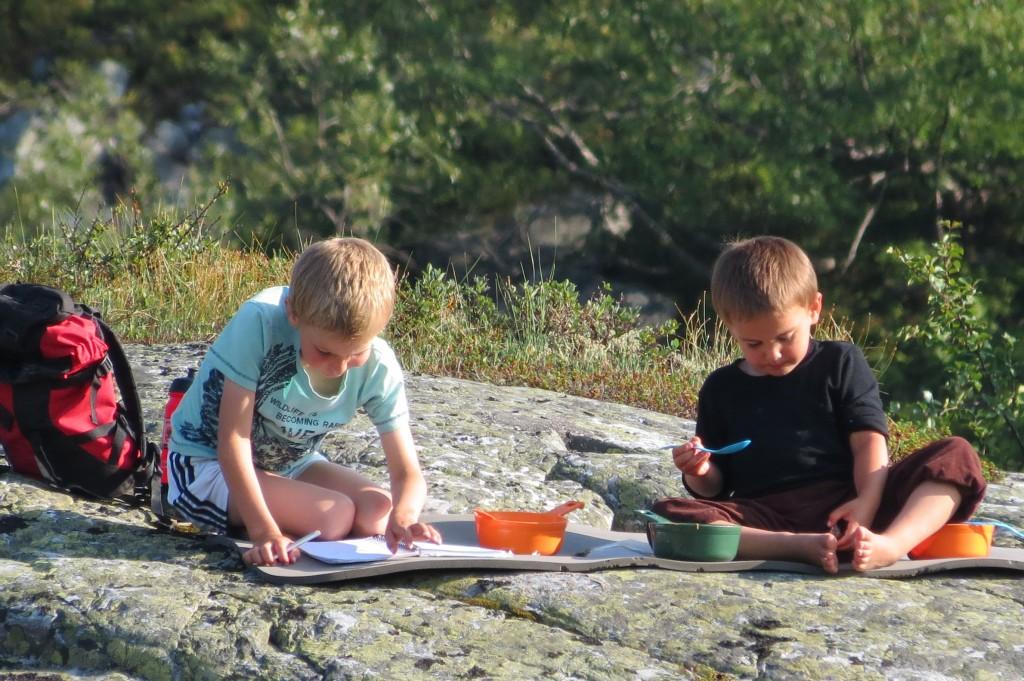 Guttene koser seg i kveldssolen med turdagboken
